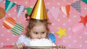 Compleanno La ragazza felice del bambino sta mangiando un dolce stock footage