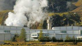 Complejo de edificios de la central eléctrica geotérmica en campo en Islandia, colinas cercanas almacen de metraje de vídeo