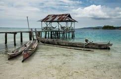Complejo playero tropical de la arena en la isla remota de Malenge, parte del archipiélago de Togean con los barcos tradicionales foto de archivo libre de regalías