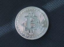 Complemento del bitcoin del metallo sul fondo blu della fibra fotografia stock libera da diritti