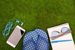 complementos - chancletas, teléfono elegante con los auriculares, cuaderno de notas, gafas de sol en la hierba imagen de archivo libre de regalías