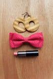 Complementos en superficie de madera Pendientes, corbata de lazo, lipsti Imágenes de archivo libres de regalías