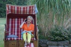 Completamente in conformità con i tempi, la giovane donna in una sedia di spiaggia di vimini coperta con lo smartphone ed il biki immagini stock libere da diritti