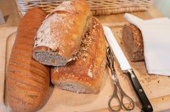 Completamente do pão recentemente cozido delicioso na placa de corte de madeira com faca e alicate fotografia de stock