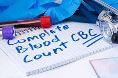 Complete Blood Count CBC test procedure. Laboratory test tubes with blood, stethoscope and gloves are near note with text Comple Stock Photo