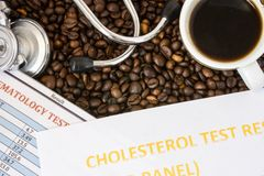 Complete blood count, cholesterol test result or lipidogram, medical stethoscope and a mug of coffee are on background of coffee b Stock Image