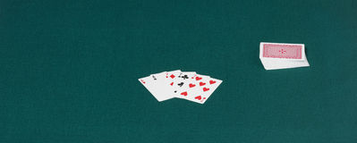 Complete card deck over a green table-hence Royalty Free Stock Photos