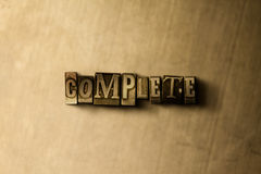 COMPLETE - close-up of grungy vintage typeset word on metal backdrop Stock Image