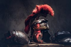 Complete combat equipment of the ancient Greek warrior lie on a box of wooden boards. Isolated on a dark background royalty free stock photography