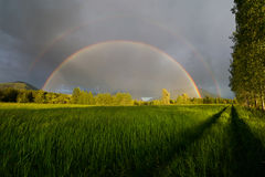 Complete Double Rainbow. In a lush green mountain field stock image