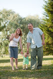 Complete family. Family of three people walking in the park Royalty Free Stock Photography