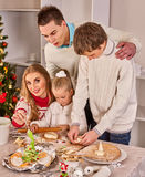 Complete family with children rolling dough in Xmas kitchen. Happy family with children rolling dough in Christmas kitchen. Complete family with two children Stock Photography