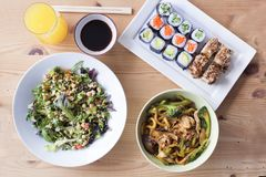 Complete healthy meal of sushi and salad on a wooden table. Complete healthy meal menu of sushi and pasta wok on a wooden table stock images