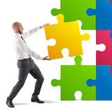 Complete a puzzle. Businessman complete a puzzle inserting last piece stock image