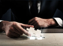 Complete a puzzle. Businessman complete a puzzle inserting last piece Stock Photo