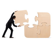 Complete a puzzle with missing piece. Businessman complete a big puzzle inserting a missing piece royalty free stock photos