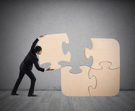 Complete a puzzle with missing piece. Businessman complete a big puzzle inserting a missing piece Stock Photos