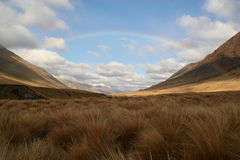 Complete rainbow over tussock grasses, New Zealand Stock Images