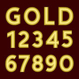 A complete set of numbers made from gold  thick wire with a matte surface. Font is isolated by a velvety dark crimson background. Stock Photos