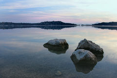 Complete silence. Lake,rocks as foreground,color-reflections in the water stock images
