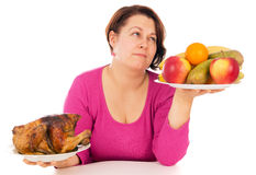 A complete woman is the choice of what to eat chicken or fruit Royalty Free Stock Images