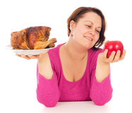 A complete woman is the choice of what to eat chicken or fruit Royalty Free Stock Image