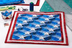 Completed quilt with stylized elements of American flag, patchwork tools Royalty Free Stock Photos