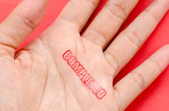 Completed stamp on hand on red background. Royalty Free Stock Image