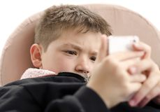 Mobile phone games. Completely absorbed little Boy playing with mobile phone on line games.  on white background Stock Photography