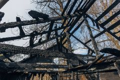 Completely burnt wooden house. Remnants of collapsed roof. Consequences of fire.  royalty free stock photo