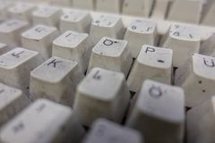 A completely dirty white computer keyboard in a workshop stock photos