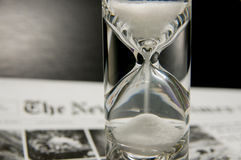 Completely filled sandglass on newspaper. With black gradient background. Sandglass on newspaper. Symbolizing the transience of time, the need for timely Stock Photos