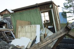 Completely ruined house, broken windows. Around different garbage, tires, boards, pieces of plywood stock photo