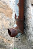 Almost completely rusted and beaten down gutter rainfall exit mounted with metal brackets on side of dilapidated cracked family royalty free stock photo