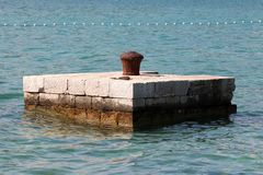 Completely rusted dilapidated iron mooring bollard in middle of stone pier surrounded with calm sea used for tying larger ships. Completely rusted dilapidated stock photos