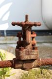 Completely rusted metal pipe connection with strong fully closed valve at abandoned industrial complex stock photo