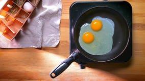Completi giù il colpo, due uova organiche su una padella che si prepara per la prima colazione e che diventa bianca sulla tavola  archivi video