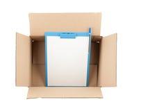 Completi giù la vista della scatola di cartone aperta con la lavagna per appunti in  Fotografia Stock