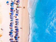 Completi giù la vista di una spiaggia con i suntbeds dei turisti ed i wi degli ombrelli fotografia stock libera da diritti