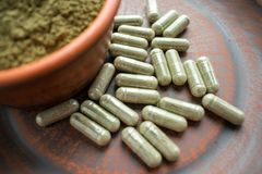 Completi le capsule e la polvere verdi del kratom sul piatto marrone erba fotografie stock libere da diritti