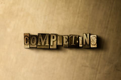 COMPLETING - close-up of grungy vintage typeset word on metal backdrop Royalty Free Stock Photography