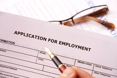 Completing an employment application. Glasses in the background Stock Photography