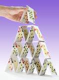 Completing a house of cards. Low-angle view of a man completing a house of cards Stock Photo