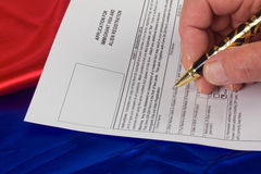 Completing Immigrant Visa. Man completing form to apply for Immigrant Visa Stock Photography