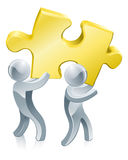Completing jigsaw teamwork. Concept of two people completing a jigsaw puzzle using teamwork Stock Images