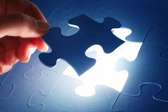 Completing the last piece of jigsaw puzzle. Solution Royalty Free Stock Photo
