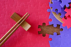 Completing the missing jigsaw puzzle. Concept, with chopstick for business concept Royalty Free Stock Photos