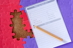 Completing the missing jigsaw puzzle. And pencil with a piece of notebook paper Stock Image