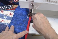 Completing mitered corner of a quilt. A quilter uses a stihletto to guide the fabric to complete a mitered corner on a quilt Royalty Free Stock Image