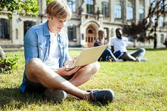 Concentrated male person working on open air. Completing task. Serious student crossing legs while sitting on the grass and preparing project Royalty Free Stock Photos